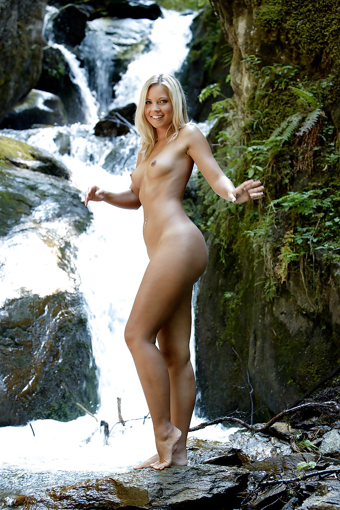 Оголенная светловолосая девушка снимается недалеко от водопада и показывает прелести секс фото