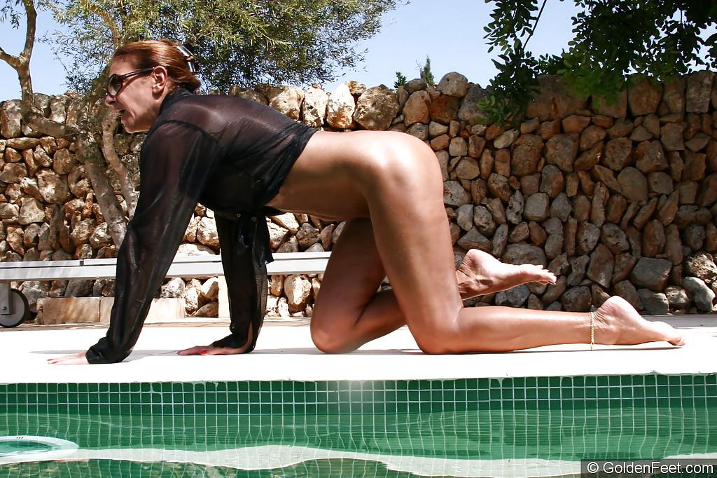 Англичанка показывает лысую киску и выпячивает задницу на фоне басейна
